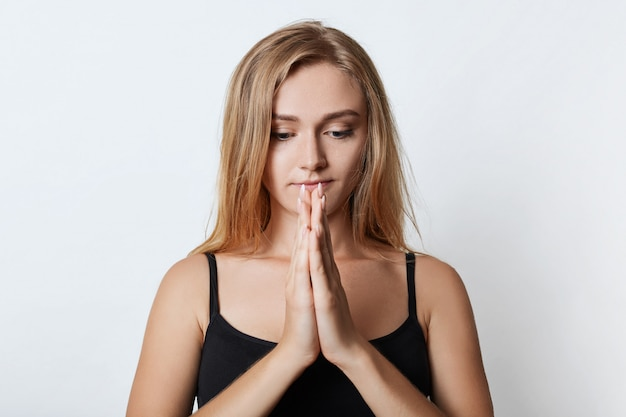 Trouwe jonge vrouw bidt voor de gezondheid van haar familie, houdt de handpalmen bij elkaar, hoopt op beter. blonde schattige vrouwelijke student maakt zich zorgen voor het eindexamen, bidt voor geluk. mensen en aanbidding concept