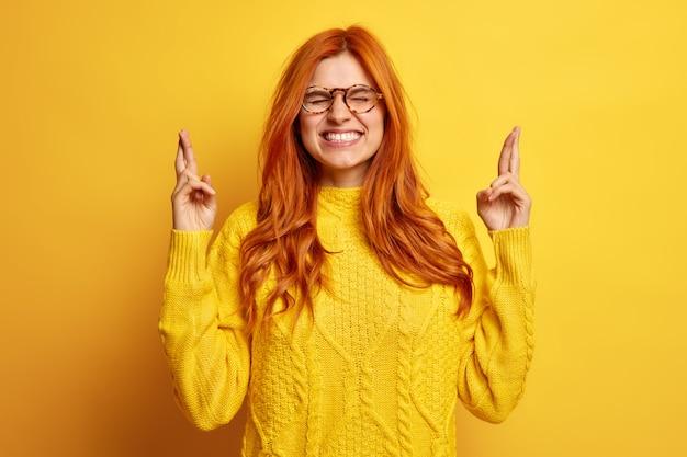 Trouwe mooie jonge roodharige vrouw sluit ogen houdt vingers gekruist maakt wens gekleed in casual trui gelooft in geluk.