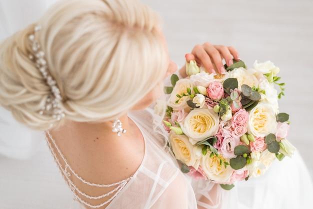 Trouwen boeket met crème en roze rozen in de handen van de bruid. delicaat bloemenclose-up. lente boeket. het uitzicht vanaf de top.