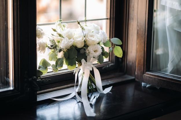 Trouwen boeket met pioenrozen en rozen op een stoel en corsages