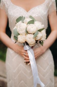 Trouwen boeket met pioenrozen in de handen van de bruid op de bruiloft.