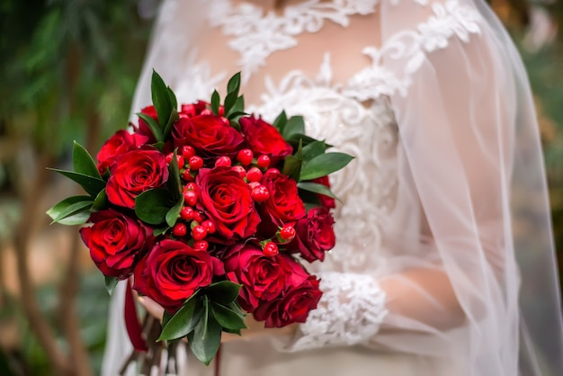 Trouwen boeket met rode bloemen in de handen van de bruid. boeket met rode bessen en rozenclose-up. winter boeket