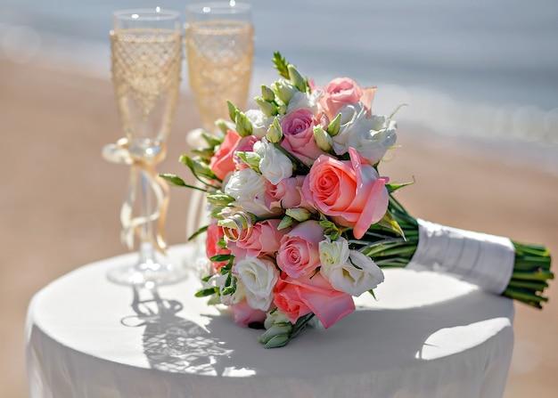 Trouwen boeket op tafel naast de glazen. bloemen op een achtergrond van zand en water.