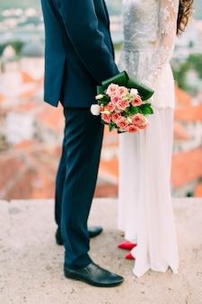 Trouwen boeket van roze rozen in handen van de bruid. bruiloft in montenegro.