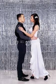 Trouwfoto. jonge bruid en bruidegom dansen op schitterende achtergrond