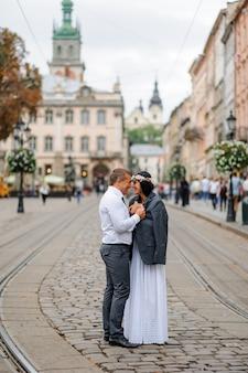 Trouwfotosessie in het centrum van de oude stad. de bruidegom gaf zijn bruid zijn jasje zodat ze zichzelf zou verwarmen. het paar knuffelt en glimlacht naar elkaar. bruiloft fotografie in rustieke stijl
