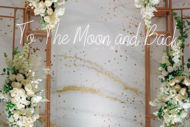 Trouwfotozone versierd met witte bloemen en groene bladeren met een inscriptie naar de maan en