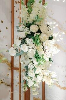 Trouwfotozone versierd met witte bloemen en groene bladeren