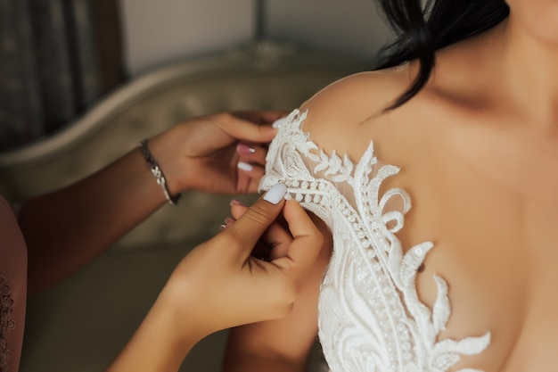 Trouwjurk details. bruid kleedt zich aan.