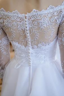Trouwjurk met veel kleine witte knoopjes vanaf de achterkant van de bruid