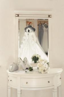 Trouwjurk op een mannequin wordt weerspiegeld in de spiegel tegen de achtergrond van schoenen, boeket en bril