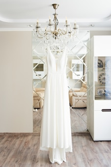 Trouwjurk opknoping op de spiegel, bruid ochtend