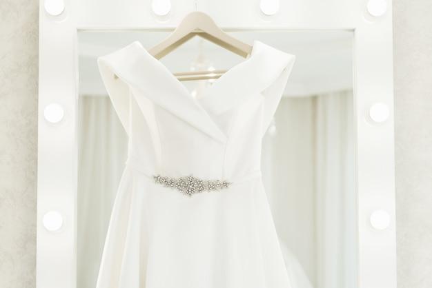 Trouwjurk opknoping op de spiegel voor de ochtend van de bruid