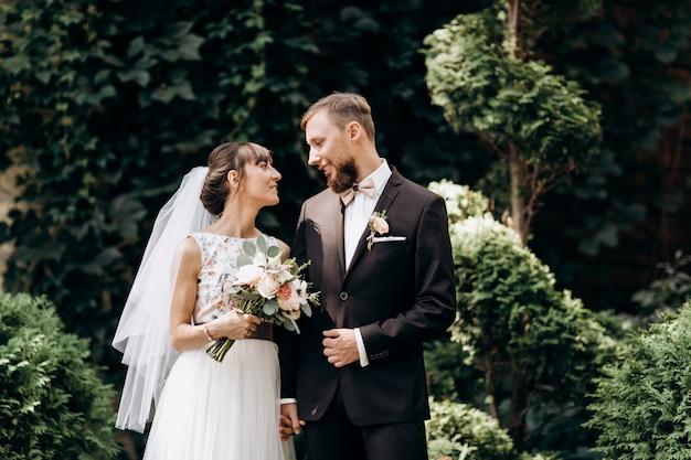 Trouwkoppel. bruid en bruidegomportret. de gelukkige bruid en de bruidegom van paarjonggehuwden bij een huwelijk in aard groen bos