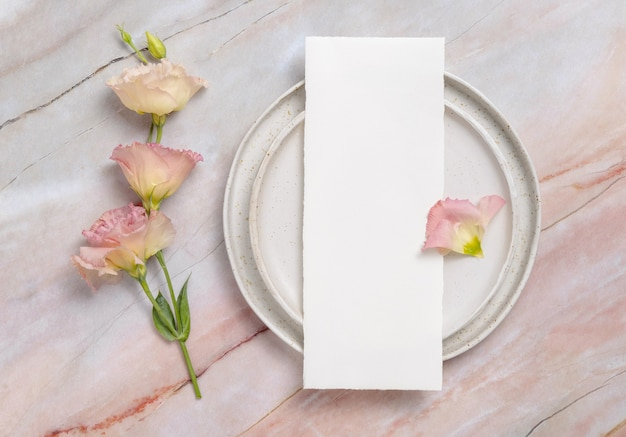 Trouwmenu liggend op een keramische plaat op een marmeren tafel versierd met bloemen en linten