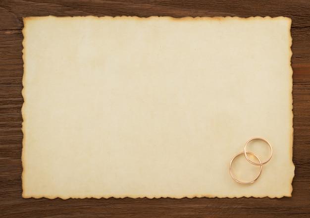 Trouwring en oud papier op hout