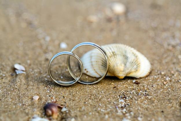 Trouwring en zeeschelp op het zandstrand