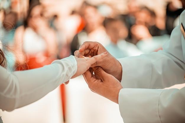 Trouwring in de handen van de bruid en bruidegom