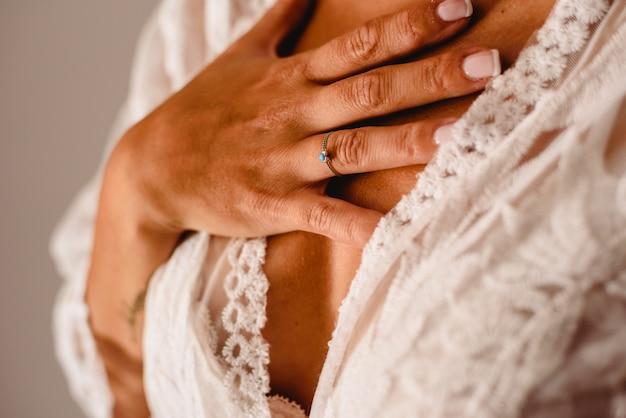 Trouwring in de handen van een vrouw met haar huwelijkskleding.