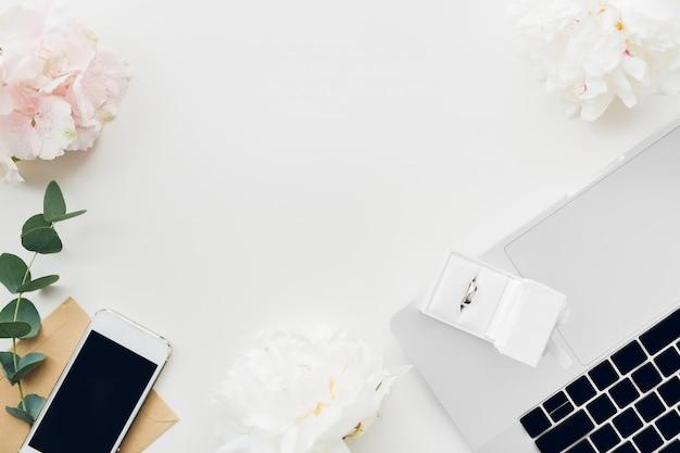 Trouwring in witte giftdoos van bloemen en telefoon. bovenaanzicht