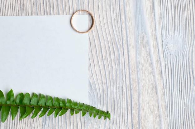 Trouwring met een vel wit papier en een groene tak op een houten achtergrond. bovenaanzicht.