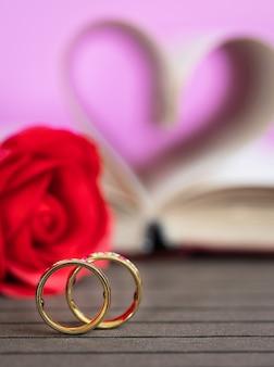 Trouwring met pagina's van boek gebogen hartvorm met rode roos