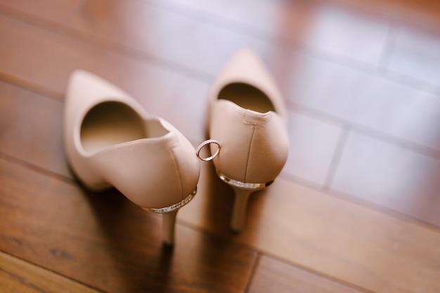 Trouwring op de crèmekleurige schoenen van de bruid op een wazig oppervlak