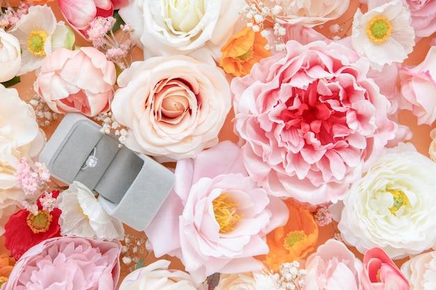Trouwring op pastelkleurige achtergrond met bloemmotief