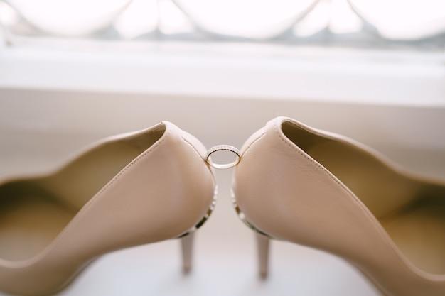 Trouwring van de bruid op een witte ondergrond met de schoenen van de bruid in beige