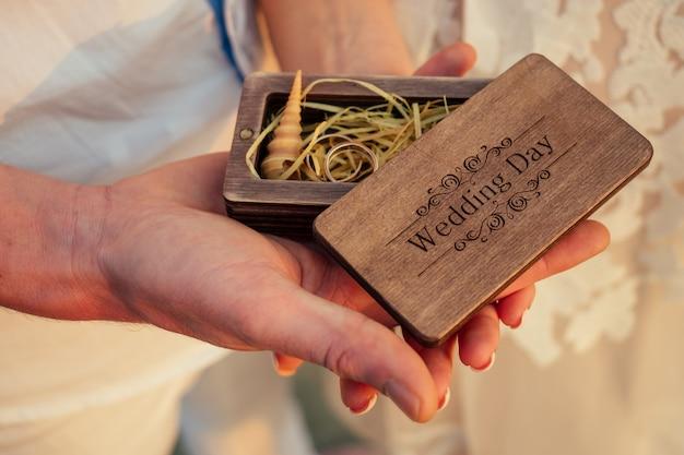 Trouwringen en een schelp in een houten kist (een bruiloft op het strand)