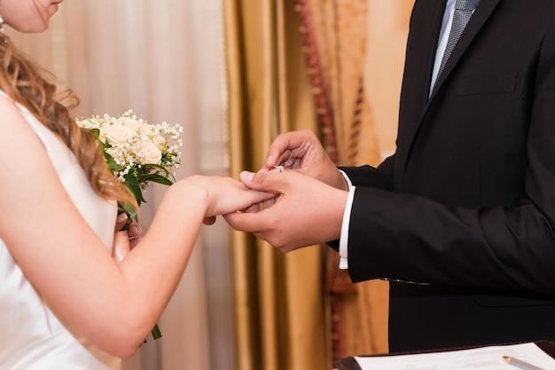 Trouwringen en handen van bruid en bruidegom. jonge bruidspaar bij ceremonie.
