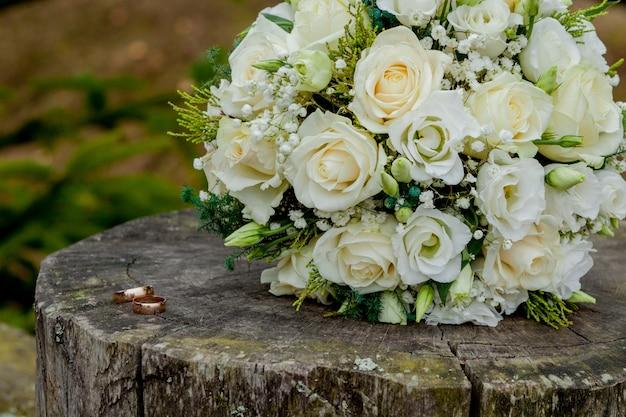 Trouwringen en het boeket van de bruid op stomp, het bruidsboeket