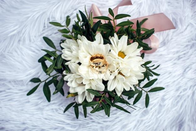 Trouwringen, goud en diamant op een witte chrysant, close-up. twee mooie ringen op de bruiloft boeket, bovenaanzicht.