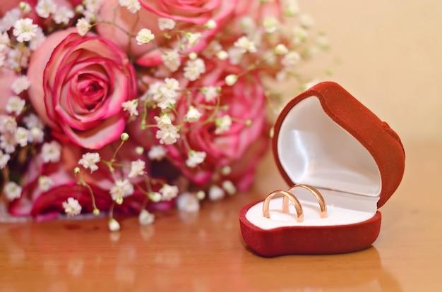 Trouwringen in een roze doos naast het boeket van de bruid