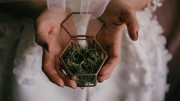 Trouwringen in een terrarium met mos dat door de handen van de bruid wordt gevangen