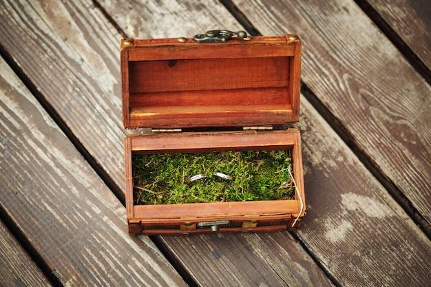 Trouwringen in houten uitstekende doos op mos