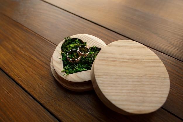 Trouwringen in ringsdoos in vorm van hart met groen mos op houten achtergrond met exemplaarruimte. rustieke bruiloft concept.