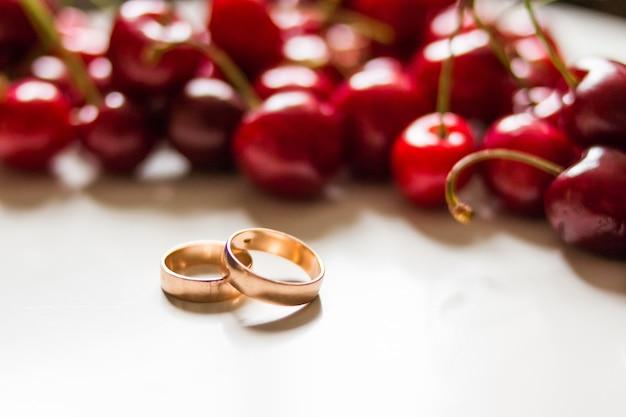 Trouwringen, kersen. bruiloft. de gouden ringen sluiten omhoog met kersenbessen zoals achtergrond. kopieer ruimte voor tekst. uitnodigingskaart.