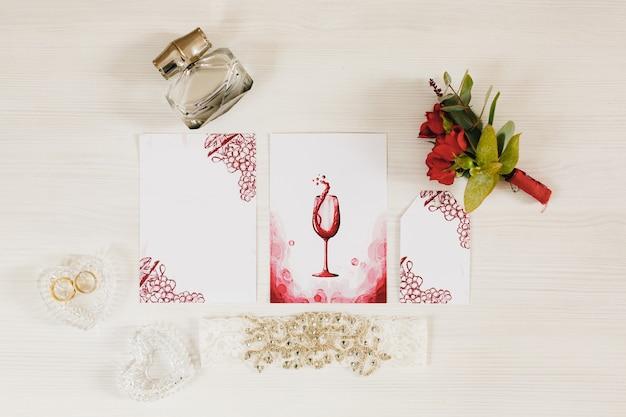 Trouwringen liggen in een hartvormige kristallen doos op de tafel vlakbij ligt een klein boeket rozen