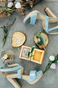 Trouwringen liggen in een houten kist omringd door sandalen met hakken, bloemen en twijgen op de grond
