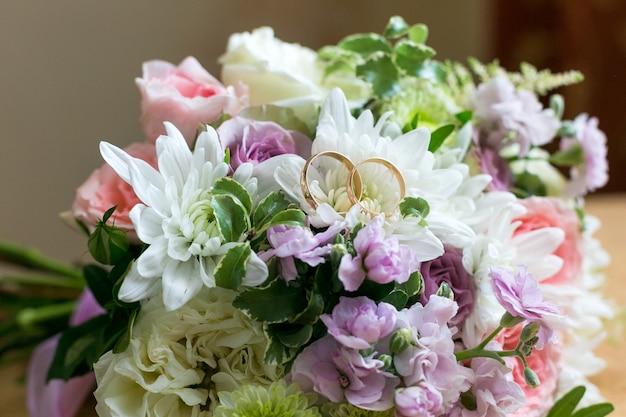 Trouwringen liggen op de bloembladen van een bruidsboeket bloemen.