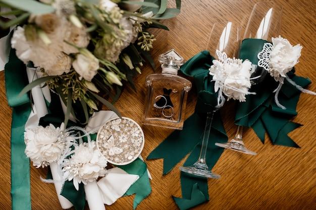 Trouwringen liggen op de parfumfles in de buurt van bloemen