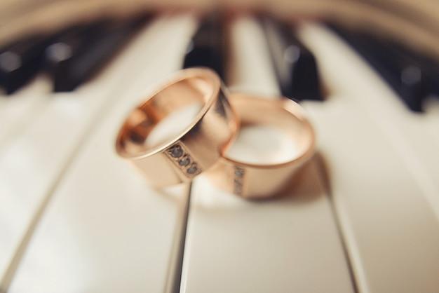 Trouwringen liggen op de piano toetsen, compositie bruiloft decor