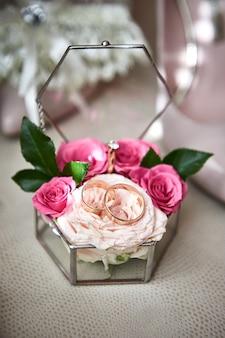 Trouwringen liggen op een mooi boeket als bruidsaccessoires