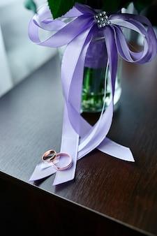 Trouwringen liggen op een mooi boeket bloemen met paarse linten