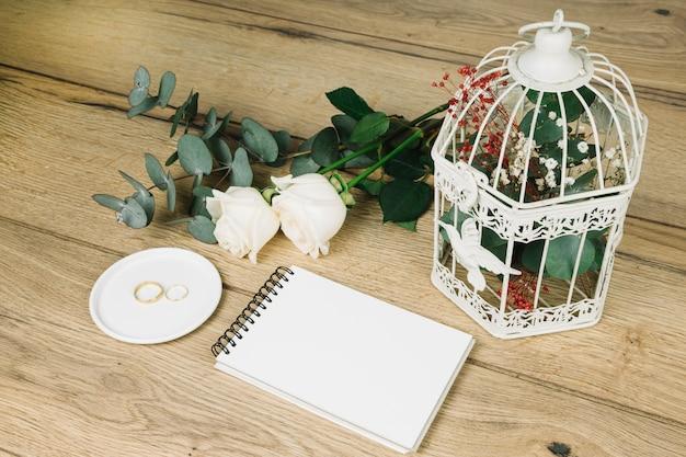 Trouwringen met bloemen en een notebook