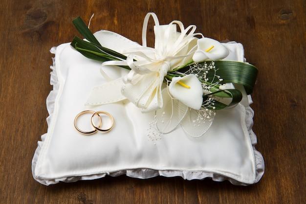 Trouwringen met calla boeket op bruids kussen