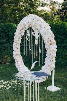 Trouwringen met een glazen juwelendoos naast een pen om te schrijven op een glazen tafel versierd met glazen kralen tegen de achtergrond van een witte bloemenboog