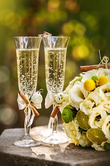 Trouwringen met rozen en glazen champagne