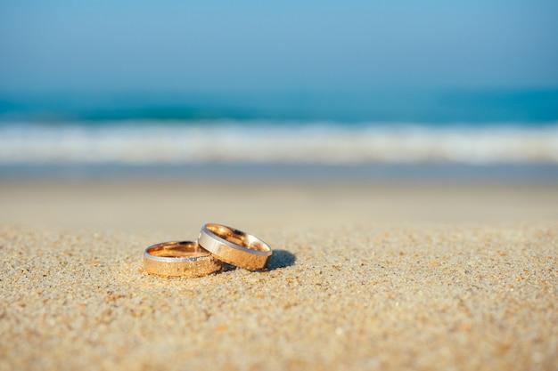 Trouwringen op de achtergrond van de zee. concept van een huwelijksceremonie op het strand.